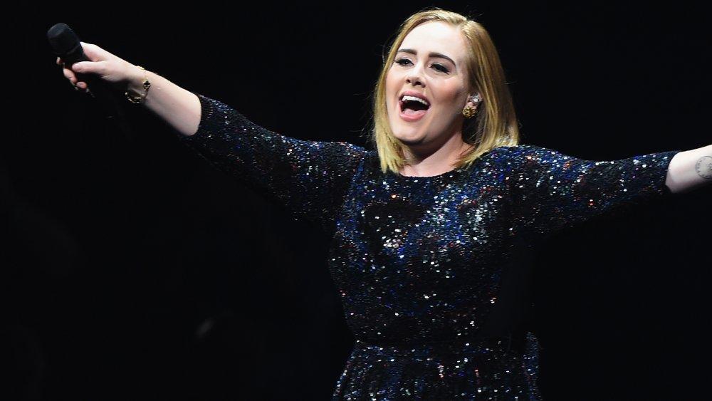 Adele lächelte auf der Bühne und zeigte mit dem Mikrofon auf ihr Publikum