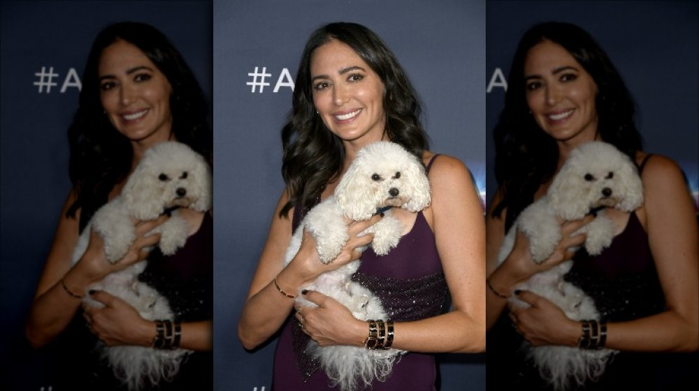 Lauren Silverman lächelt, während sie ihren Hund hält