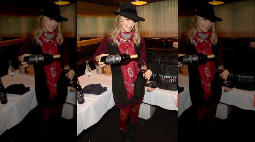 Fergie hält eine Flasche Wein