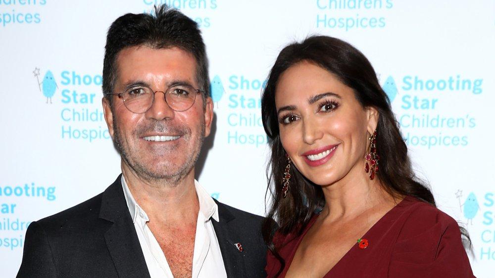 Simon Cowell und Lauren Silverman lächeln und posieren Arm in Arm