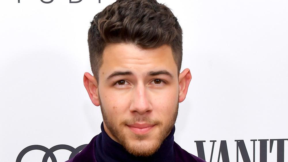 Nick Jonas posiert für Kameras und lächelt leicht