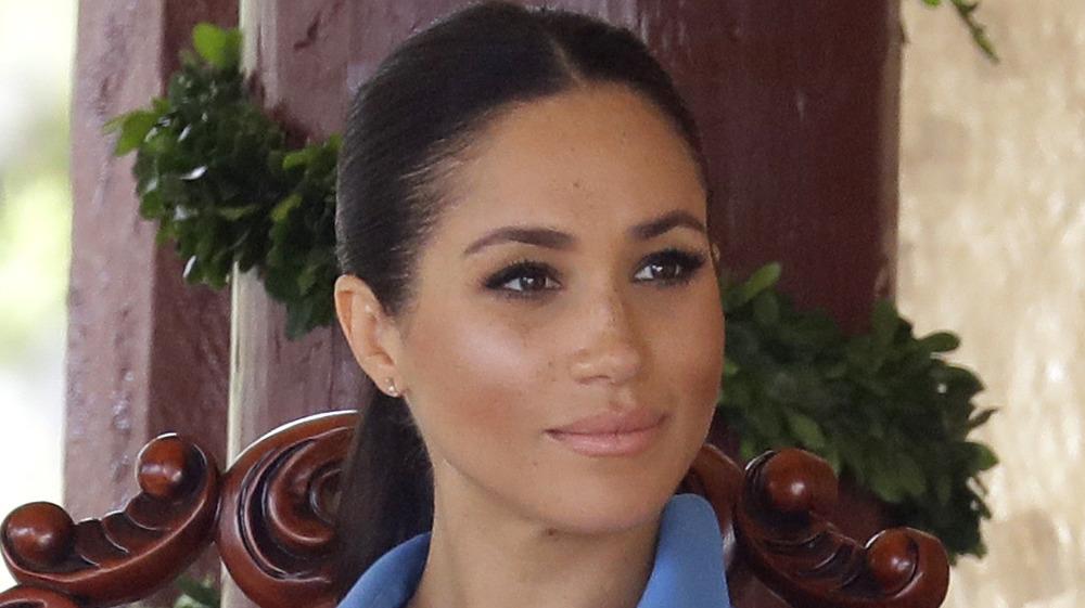 Meghan Markle trägt einen Pferdeschwanz und ein blaues Kleid