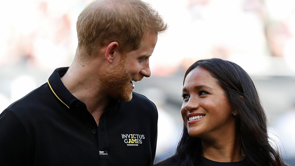 Prinz Harry und Meghan Markle lächeln sich an