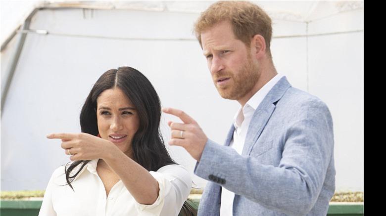 Meghan Markle und Prince Harry zeigen mit den Fingern