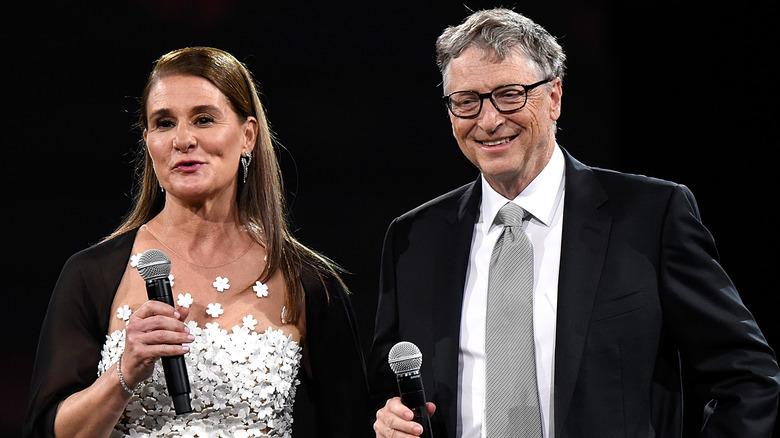 Melinda und Bill Gates sprechen und lächeln mit Mikrofonen