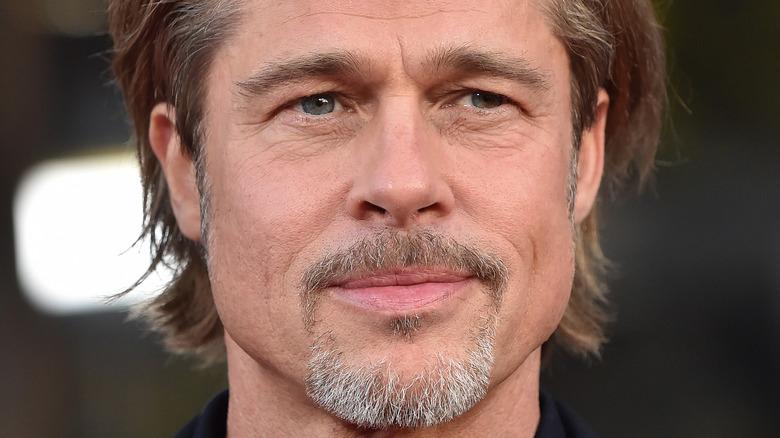Brad Pitt trägt einen ungepflegten, grauen Bart und lächelt