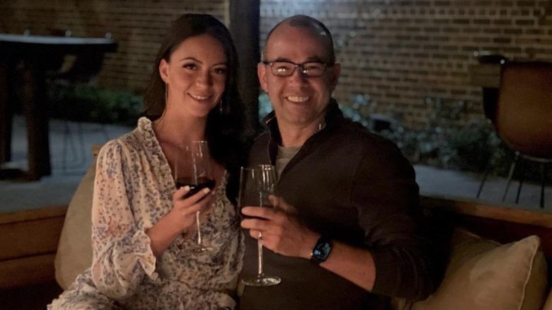 Melyssa Davies und James Murray lächeln mit einem Glas Wein