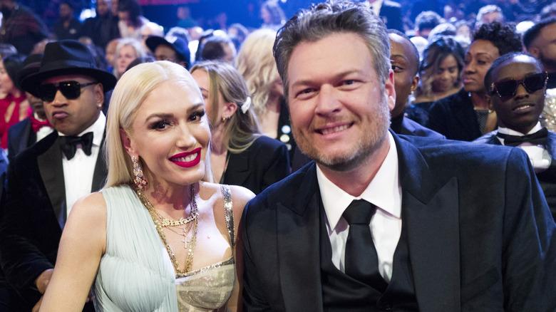 Gwen Stefani und Blake Shelton sitzen und posieren