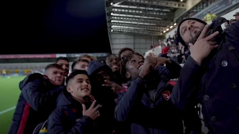 Adam Richman posiert mit Fans beim Fußballspiel