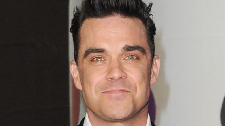 Robbie Williams grinst
