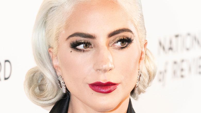 Lady Gaga mit rotem Lippenstift und leichtem Lächeln auf dem roten Teppich