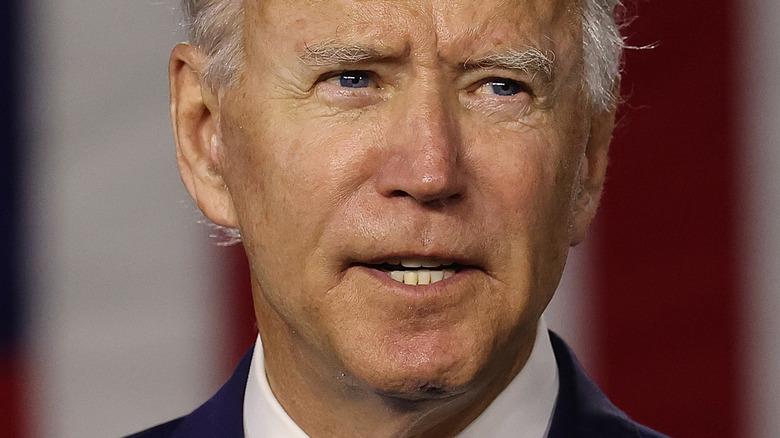 Joe Biden mit ernster Miene vor amerikanischer Flagge