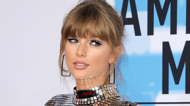 Taylor Swift lächelt leicht mit hochgesteckten Haaren und rosa Lippenstift