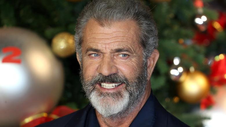 Mel Gibson grinst an einem Weihnachtsbaum