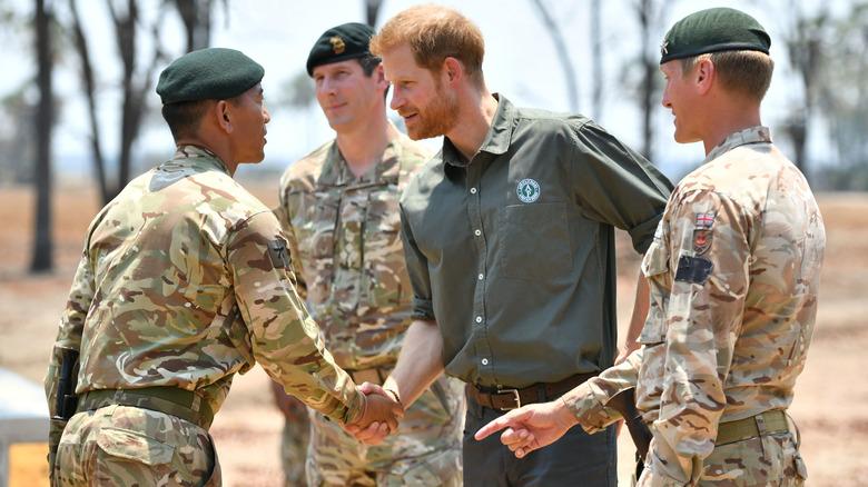 Prinz Harry schüttelt einem Militäroffizier die Hand