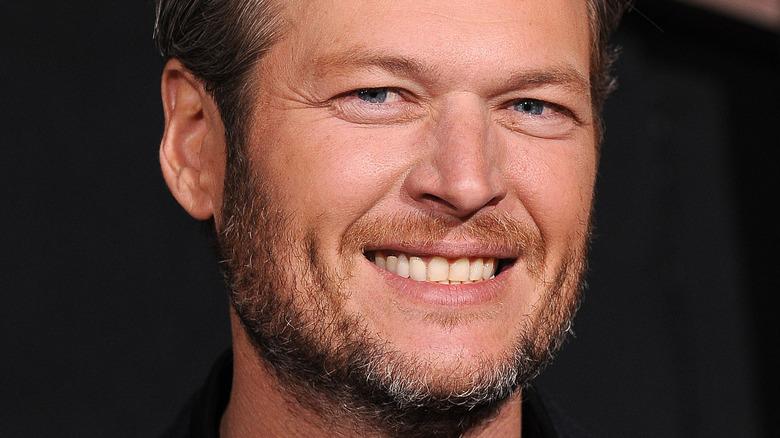 Blake Shelton lächelt im dunklen Anzug.