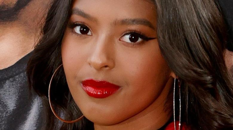 Natalia Bryant mit leichtem Lächeln und rotem Lippenstift