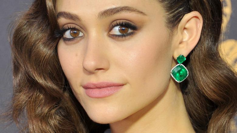 Emmy Rossum lächelt und trägt grüne Ohrringe